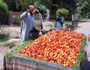 فیصل آباد: ریڑھی بان فروٹ کو تازہ رکھنے کے لیے پانی کا چھڑکاؤ کر رہا ..