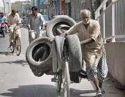 ملتان: ایک معمر محنت کش سائیکل پر استعمال شدہ ٹائر رکھے جا رہا ہے۔
