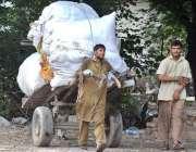 راولپنڈی: نوجوان محنت کش ہتھ ریڑھی پر بھاری سامان رکھے لیجا رہا ہے۔