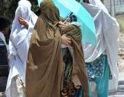 پشاور: ایک خاتون اپنے بچے کے ہمراہ گرمی اور دھوپ کی شدت سے بچنے کے لیے ..
