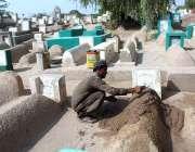 ملتان: مزدور قبر پر مٹی کا لیپ کر رہاہے۔