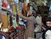 لاہور: دکاندار گاہکوں کو متوجہ کرنے کے لیے ٹوپیاں اور تسبیاں سجارہا ..