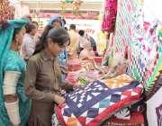 لاہور: ایک لڑکی ایکسپو سنٹر میں جاری نمائش میں تھر کی ثقافت کے حوالے ..