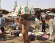 لاہور: سبزی منڈی میں ایک محنت کش وزنی سامان اٹھائے جا رہا ہے۔
