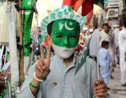 پشاور: یوم آزاد کی کی آمد کے حوالے سے ایک نوجوان ماسک پہنے وکٹری کا نشان ..