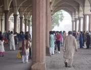 لاہور: شاہی قلعہ میں سیرو تفریح کے لیے آئے شہری بارش سے بچنے کے لیے دیوان ..