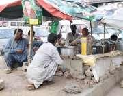 لاہور: شہری داتا دربار کے قریب سڑک کنارے قائم دکان سے چائے پی رہے ہیں۔