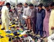 فیصل آباد: شہری سڑک کنارے لگے سٹال سے جوتے خرید رہے ہیں۔