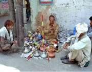 لاہور: ایک محنت کش سڑک کنارے بیٹھا حکے مرمت کر رہا ہے۔