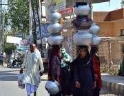 سرگودھا: خانہ بدوش خواتین اپنے سرو پر دیگچیاں رکھے اونٹنی کا دودھ فروخت ..