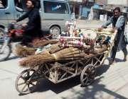 پشاور: محنت کش ہتھ ریڑھی پر گھریلو استعمال کی اشیاء رکھے فروخت کے لیے ..