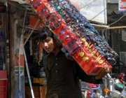 راولپنڈی: محنت کش دھوپ کے چشمے اٹھائے فروخت کے لیے جا رہا ہے۔