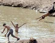 راولپنڈی: بچے گرمی کی شدت کم کرنے کے لیے تالابی پانی میں نہا رہے ہیں ..