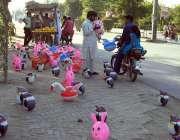 فیصل آباد: موٹر سائیکل سوار سڑک کنارے لگے سٹال سے کھلونے پسند کر رہا ..