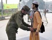 لاہور: پنجاب اسمبلی کے اجلاس کے موقع پر پولیس اہلکار ایک نوجوان کی تلاشی ..