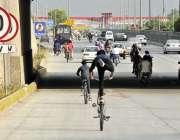 اسلام آباد: لڑکے سائیکل پر ون ویلنگ کرتے ہوئے جارہے ہیں جو کسی حادثے ..
