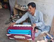 فیصل آباد: محنت کش اپنی ورکشاپ میں ہارمونیم بنا رہا ہے۔
