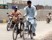 پشاور: نوجوان سائیکل سوار دوسری سائیکل کو تھامے لیجا رہا ہے۔