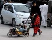 راولپنڈی: ایک خانہ بدوش خاتون معذور شخص کو ریڑھی پر لٹائے مری روڈ سے ..