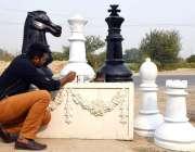 لاہور: ایک پینٹر سڑک کنارے بیٹھا نقش نگاری کر رہا ہے۔