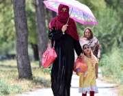 اسلام آباد: وفاقی دارالحکومت میں ایک خاتون اپنے بچی کے ہمراہ دھوپ کی ..
