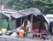 اسلام آباد: خانہ بدوش شخص بارش سے بچنے کے لیے اپنے خیمے میں بیٹھا ہے۔