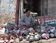 فیصل آباد: محنت کش اپنی دکا ن پر حکے کی ٹوپیاں تیار کر رہا ہے۔