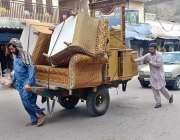راولپنڈی: محنت کش ہتھ ریڑھی پر صوفے رکھے لیجا رہا ہے۔