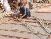 لاہور: ایک محنت کش لکڑ ی کادروازہ تیار کر رہا ہے۔