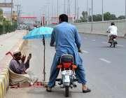 ملتان: موٹرسائیکل سوار ایک بھکاری کی مدد کر رہا ہے۔