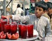 ملتان: محنت کش بچہ گاہکوں کو متوجہ کرنے کے لیے انار کا جوس فروخت کررہا ..