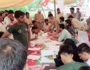 لاہور: عام انتخابات 2018  تحریک انصاف کے کیمپ میں ووٹرز اپنے ووٹ کی پرچی ..