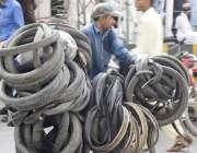لاہور: ایک محنت کش سائیکل پر پرانے ٹائر اور ٹیوبز رکھے جار ہا ہے۔