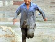 ملتان: بچہ بارش کے دوران کھیل کود میں مصروف ہے۔