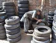 حیدر آباد: محنت کش استعمال شدہ ٹائر کو فروخت کے لیے دھو رہا ہے۔