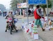 لاہور: مسلم ٹاؤن میں ایک شخص نے سڑک کنارے برتن فروخت کرنے کے لیے سجا ..