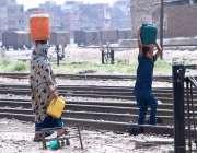 حیدر آباد: خانہ بدوش خاتون اپنی بچی کے ہمراہ پینے کے لیے پانی بھر کر ..
