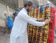 لاہور:ایک محنت کش عینکیں فروخت کرنے کے لیے سڑک کنارے کھڑا ہے۔