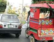 فیصل آباد: چنگچی موٹر سائیکل سوار خراب ہونے والا کار کو دھکا لگا رہاہے۔