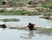 پشاور: ایک بچہ مچھلی پکڑنے کی کوشش کر رہا ہے۔