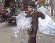 لاہور: خانہ بدوش بچہ تھیلے میں کار آمد اشیاء اکٹھی کر کے لیجا رہا ہے۔