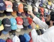 لاہور: ایک شخص دھوپ سے بچنے کے لیے ٹوپی خرید رہا ہے۔