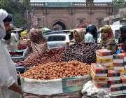 لاہور: خواتین ریڑھی بان سے کھجوریں خرید رہی ہیں۔