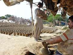 LAHORE: An artisan busy in preparing clay made pots at his workplace.