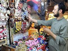 PESHAWAR: A shopkeeper arraigning and displaying children footwear to attract the customers at his roadside stall in Sadar Bazar.