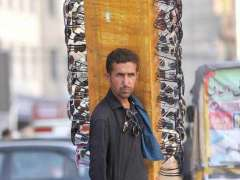 ISLAMABAD: A vendor carrying sunglass to attract the customers along the roadside in the federal capital.
