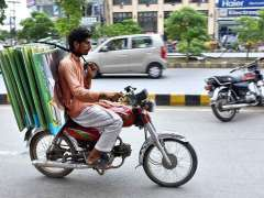 LAHORE: A worker carrying the posters for candidates of political parties for election campaign on the motorcycle at Allama Iqbal Road in the Provincial Capital.
