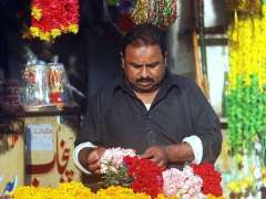 RAWALPINDI: A vendor preparing flower garlands for sell at his selling point.