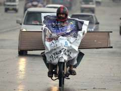 RAWALPINDI: A motorcyclist on the way under the cover of plastic sheet to protect from rain.