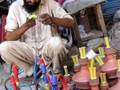 SARGODHA: A vendor assembling different parts of the traditional smoking instrument (Huqqa) at his roadside setup.
